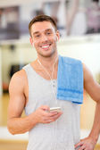 Young man with smartphone and towel in gym — Stock Photo