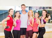Groep van gelukkige mensen in de sportschool met flessen water — Stockfoto