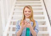 女子学生のスマート フォンでの笑みを浮かべてください。 — ストック写真