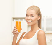 Smiling woman holding glass of orange juice — Stock Photo