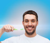 Smiling young man with toothbrush — Stock Photo