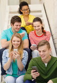 Smiling students with smartphone texting at school — Stock Photo
