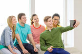 Smiling students making picture with tablet pc — Stock Photo