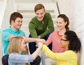 互いの上に手を持つ学生の笑みを浮かべてください。 — ストック写真