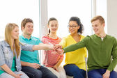 Smiling students with hands on top of each other — Stock Photo