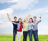 Groupe d'étudiants souriants, agitant les mains — Photo