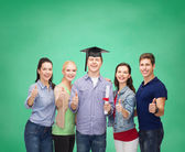 Group of students with diploma showing thumbs up — Stockfoto