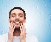 Beautiful smiling man touching his face — Foto de Stock