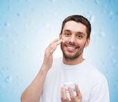 Beautiful smiling man applyin cream — Stock Photo