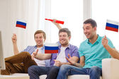 Happy male friends with flags and vuvuzela — Stock Photo