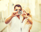 Travelling couple taking photo picture with camera — Stock Photo