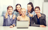 Smiling students with laptop showing thumbs up — Stock Photo