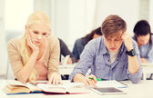 Tired students with tablet pc, notebooks and books — Stock Photo