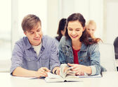 Two teenagers with notebooks and book at school — Stock Photo
