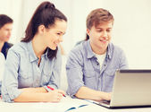 Students with laptop and notebooks at school — Stock Photo