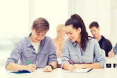 Two teenagers with notebooks at school — Stock Photo