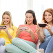 Smiling teenage girls with smartphones at home — Stock Photo #47015081