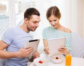 Lächelnd paar mit Tablet-pc lesen Nachrichten — Stockfoto