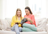Two girlfriends reading magazine at home — Stock Photo