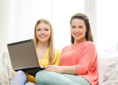 Two smiling teenage girls with laptop at home — Stock Photo