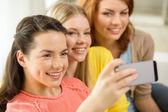 随着智能手机在家里微笑着十几岁的女孩 — 图库照片