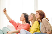 Smiling teenage girls with smartphone at home — Foto de Stock