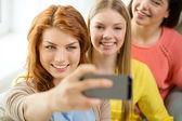 Adolescentes souriantes avec le smartphone à la maison — Photo