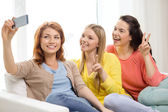 Smiling teenage girls with smartphone at home — Stock Photo