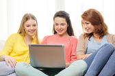 Three smiling teenage girls with laptop at home — Stock Photo