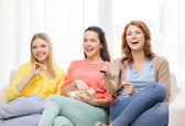 Three smiling teenage girl watching tv at home — Stock Photo