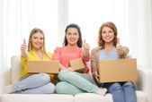 Smiling teenage girls with cardboard boxes at home — Stock Photo