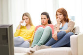 Three sad teenage girl watching tv at home — Stock Photo