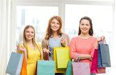 Lachende tienermeisjes met veel shopping tassen — Stockfoto