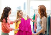 Three smiling friends trying on some clothes — Stock Photo