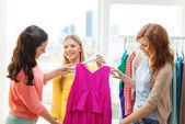 Tři usmívající se přátelé se snaží o nějaké oblečení — Stock fotografie