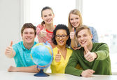 Five smiling student with earth globe at school — Stock Photo