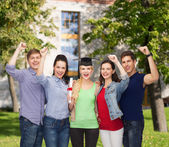 Group of standing smiling students with diploma — Stock Photo
