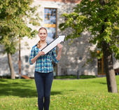 Smiling young woman with arrow poiting up — Stock Photo