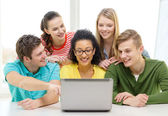 Smiling students looking at laptop at school — Stock Photo