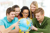 Five smiling student looking at globe at school — Stock Photo