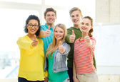 Five smiling showing thumbs up at school — Stock Photo