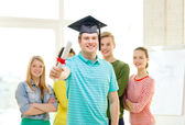 Smiling male student with diploma and corner-cap — Stock Photo