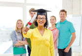 Smiling female student with diploma and corner-cap — Stock Photo