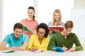 Estudiantes con los libros de texto y libros en la escuela — Foto de Stock