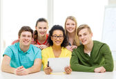 Smiling students with tablet pc computer at school — Stock Photo