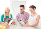 Smiling team with table pc and laptop in office — Stock Photo