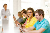 Smiling female students with tablet pc at school — Stock Photo