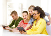 Smiling students looking at tablet pc at school — Stock Photo
