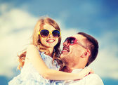 Happy father and child in sunglasses over blue sky — Stock Photo