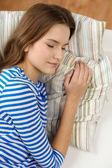 Gülümseyen genç kız evde kanepede uyuyor — Stok fotoğraf